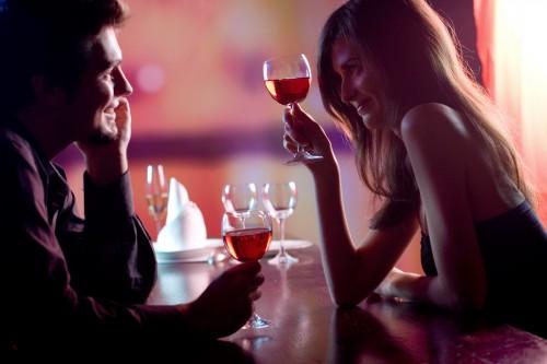 Ein verliebtes Paar teilt sich eine Flasche Wein bei einem romantischen Abendessen